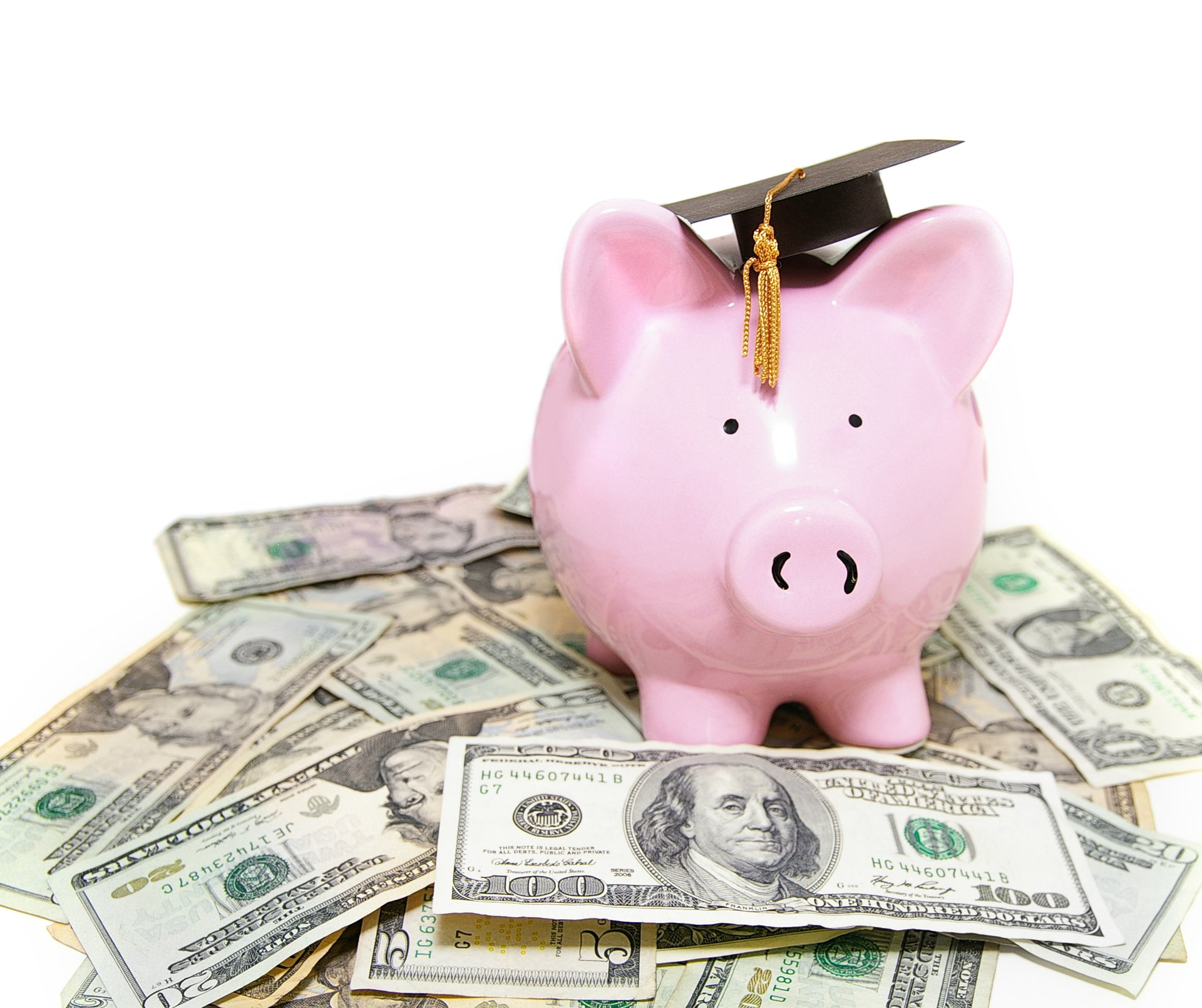 Piggybank with mortarboard on a pile of bills.