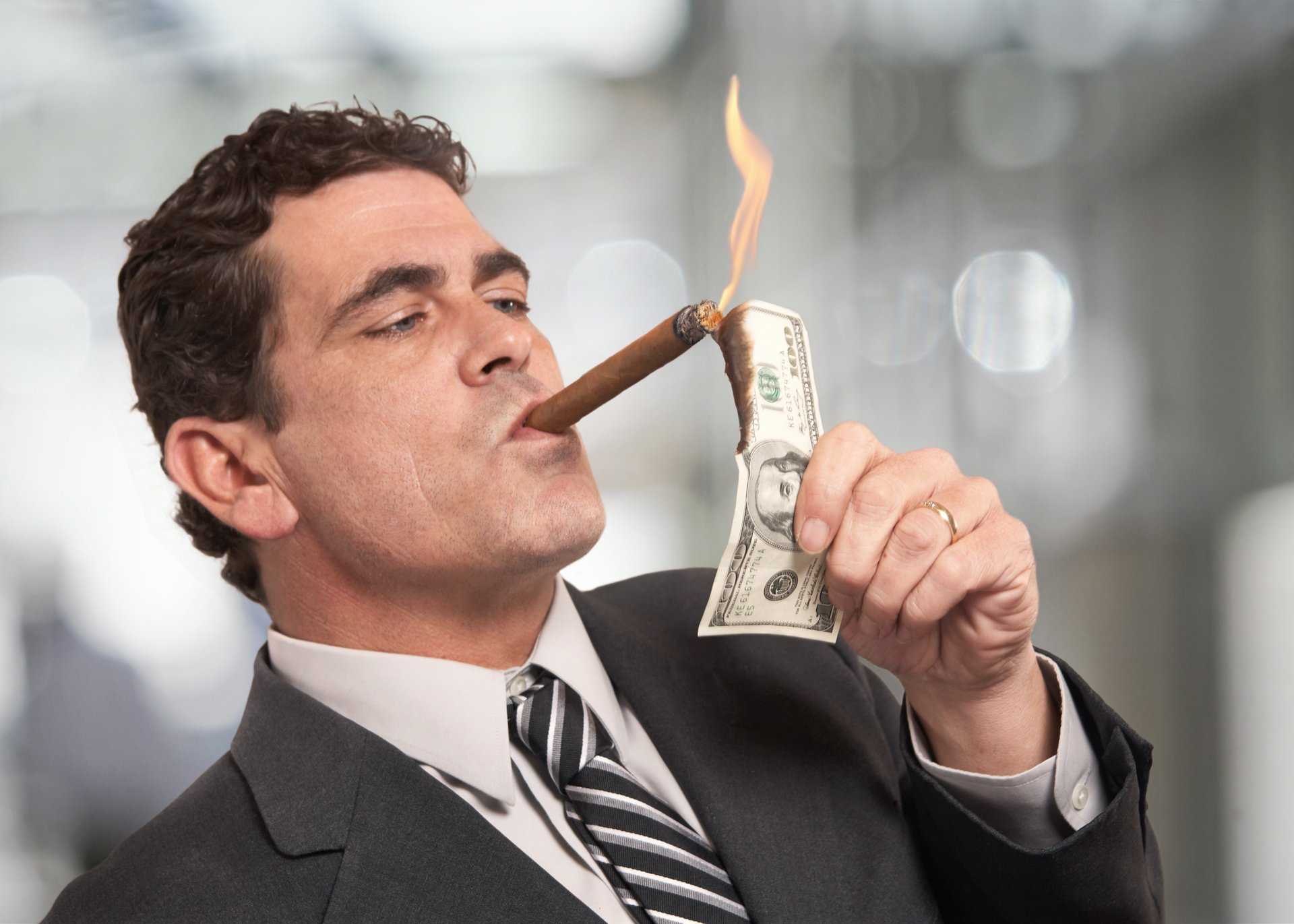 Businessman lighting a cigar with money