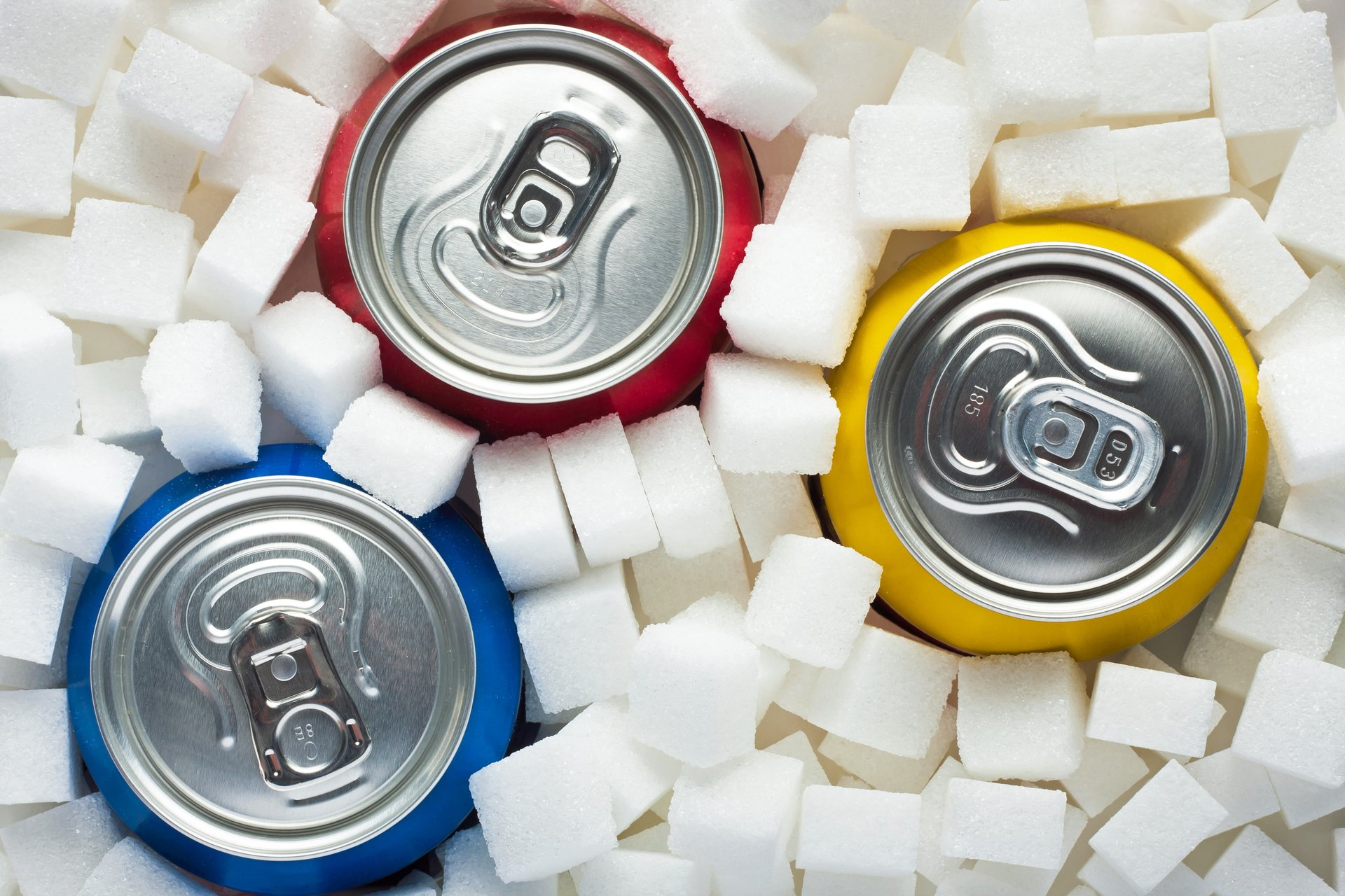 Soda cans surrounded by sugar