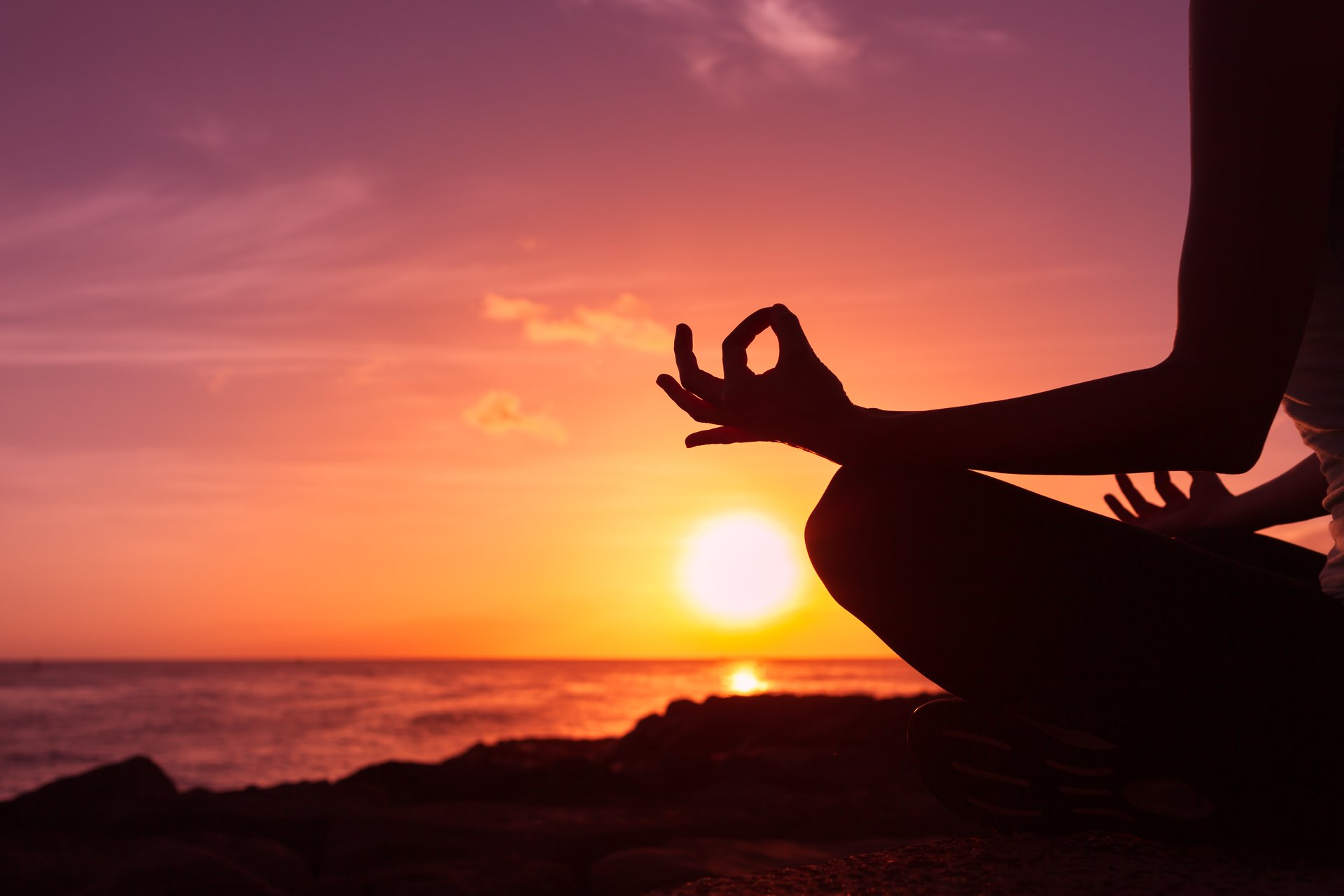 Person meditating at sunset.