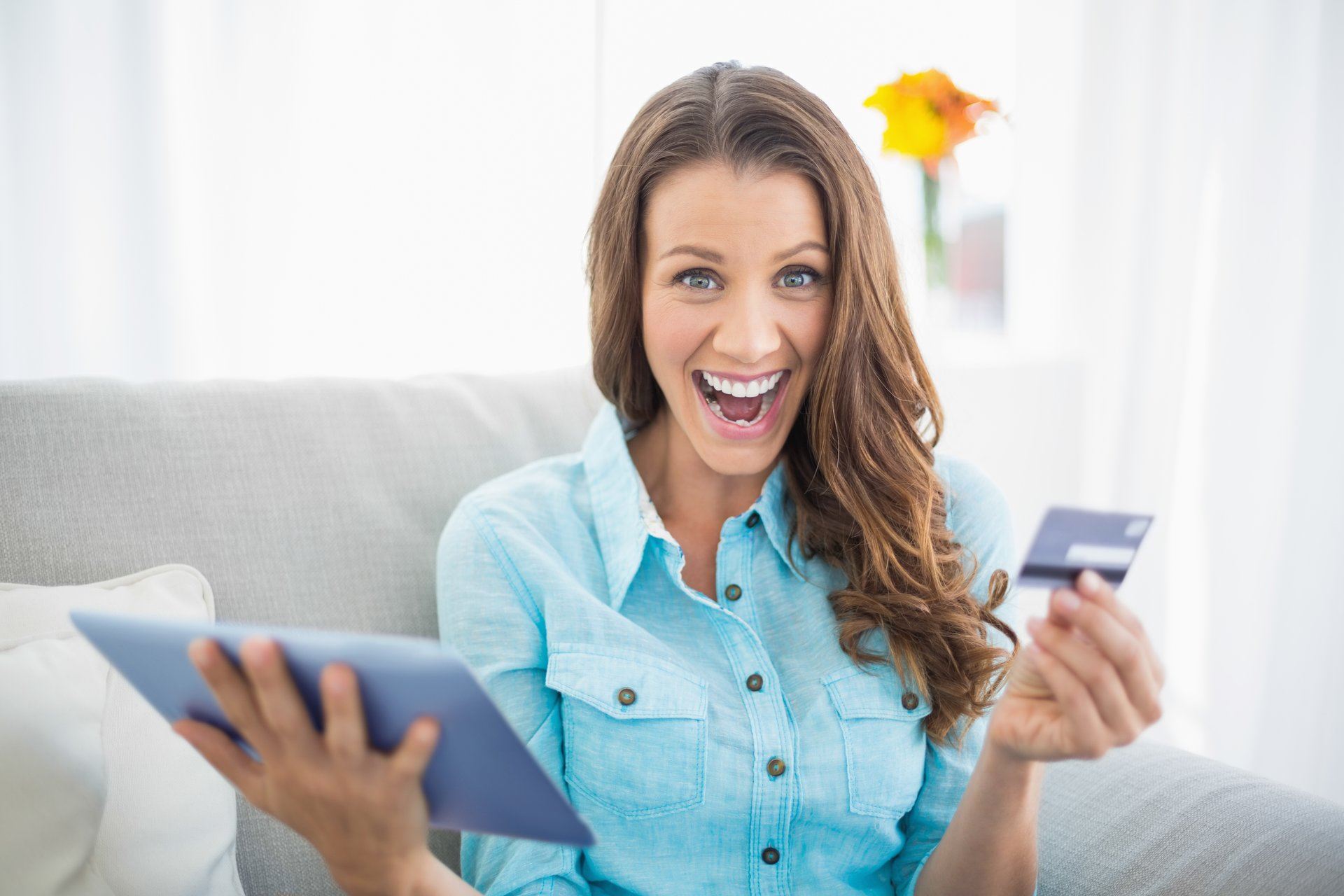 Happy woman with computer, credit card.