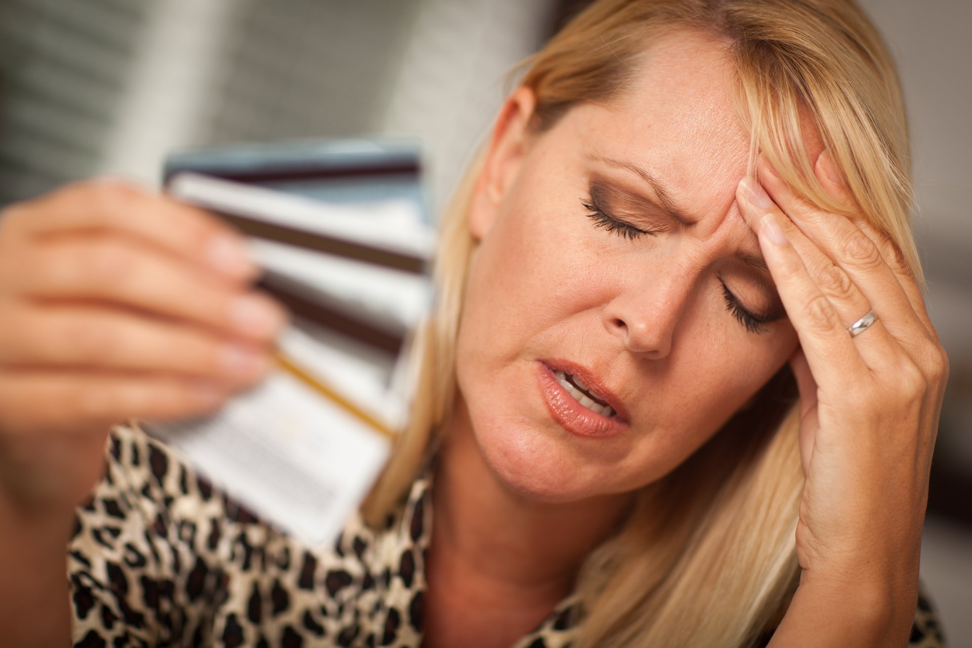 Depressed-looking woman with hand full of credit cards.