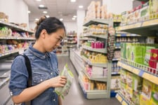 Woman considering options in a dollar store or grocery store