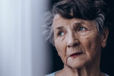 Senior standing beside window