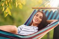 Happy woman relaxing in a hammock outdoors