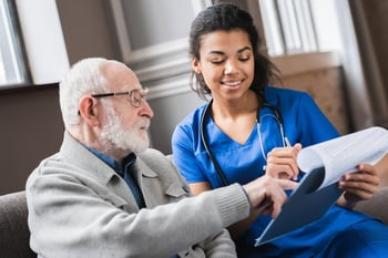 Nurse helping a senior fill out medical paperwork