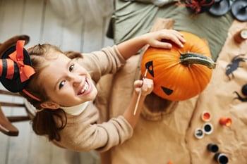 Girl painting pumpkin