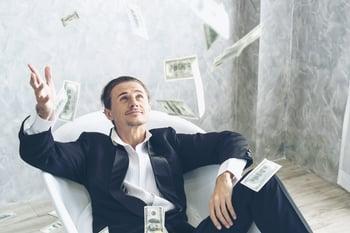 Happy businessman throwing money in a bathtub