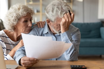 Worried senior couple reviewing documents