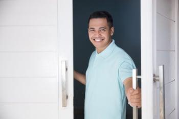 Happy man opening the front door of his home