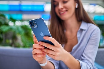 Woman smiling and using iPhone smartphone