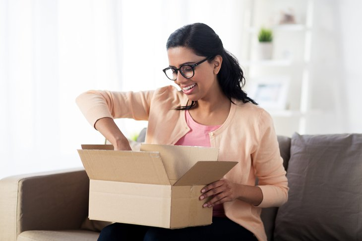 A young woman opens a package she received quickly with overnight shipping