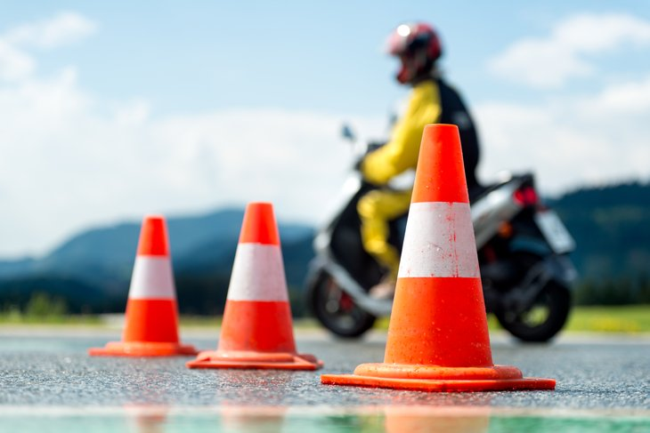 Motorcycle driving among traffic cones.