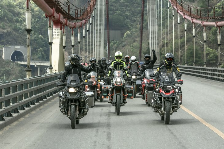 Group of BMW motorcyclists crossing a bridge.