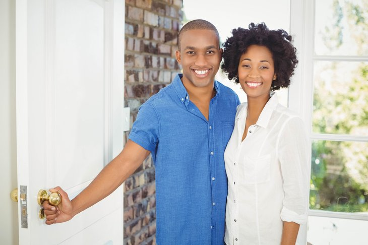 African American couple opening door to their home.