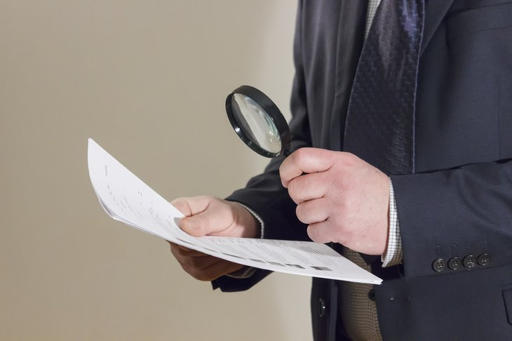 Reading paperwork with a magnifying glass.
