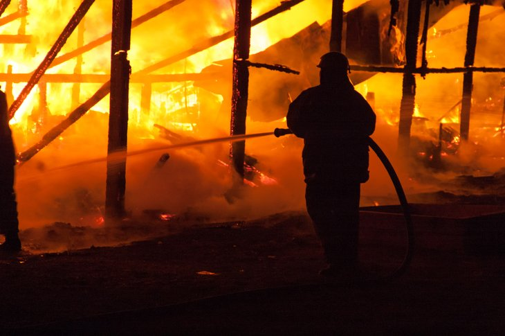 A firefighter extinguishes a house fire