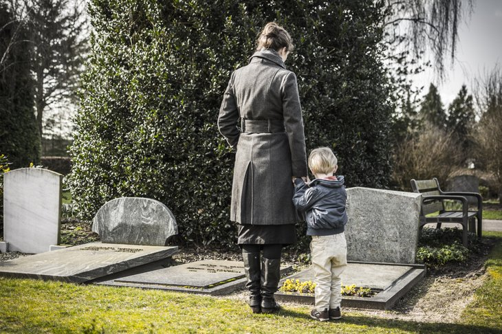 A woman and child visit a grave in a cemetery