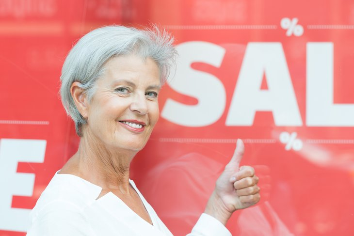 A senior woman gives a thumbs-up in front of a sale sign