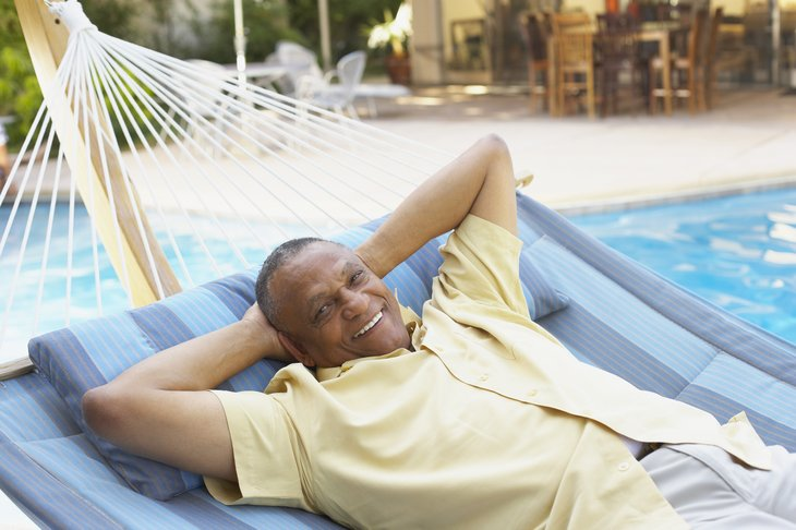 A black man relaxes in a hammock next to a pool