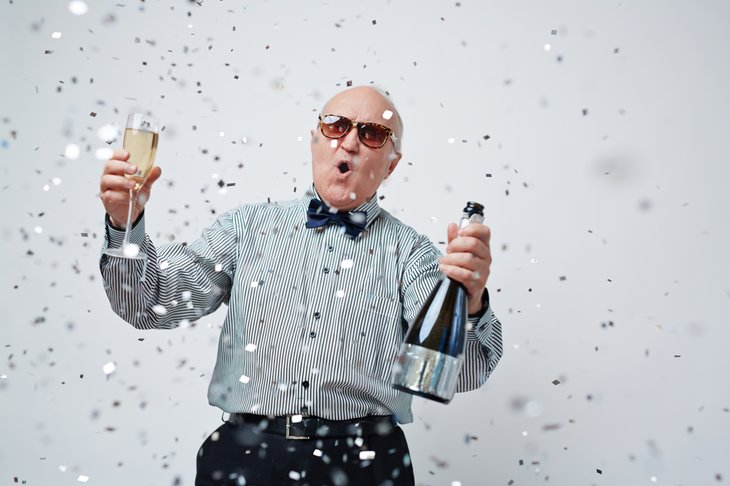 A happy senior celebrates with champagne