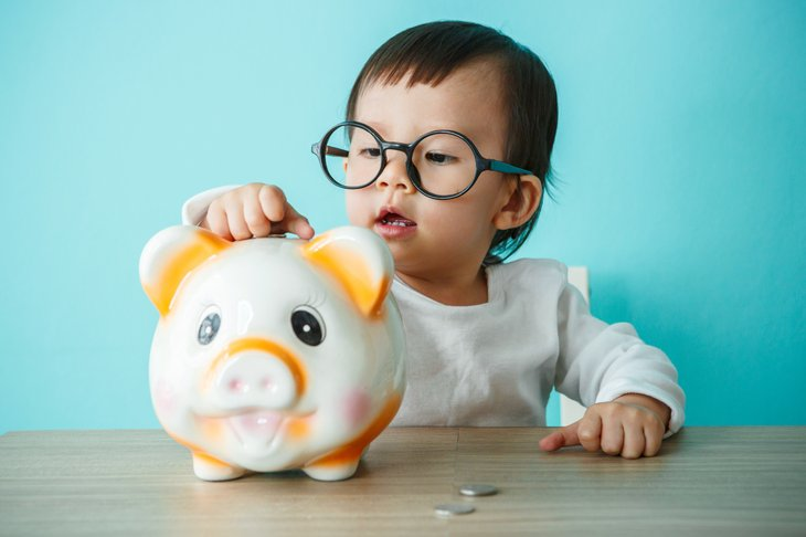 A child adds coins to a piggy bank