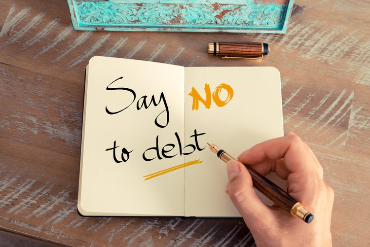 """Say no to debt"" is written in a notebook"