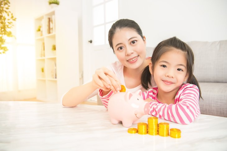 A mother helps her child fill a piggy bank