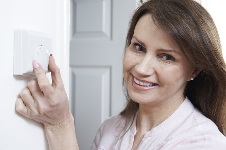 A woman adjusts a thermostat