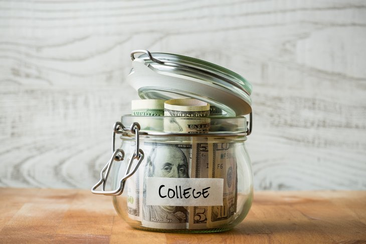"""A savings jar labeled """"college"""" is stuffed with cash"""