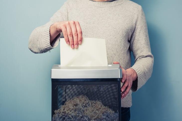A man shreds paper