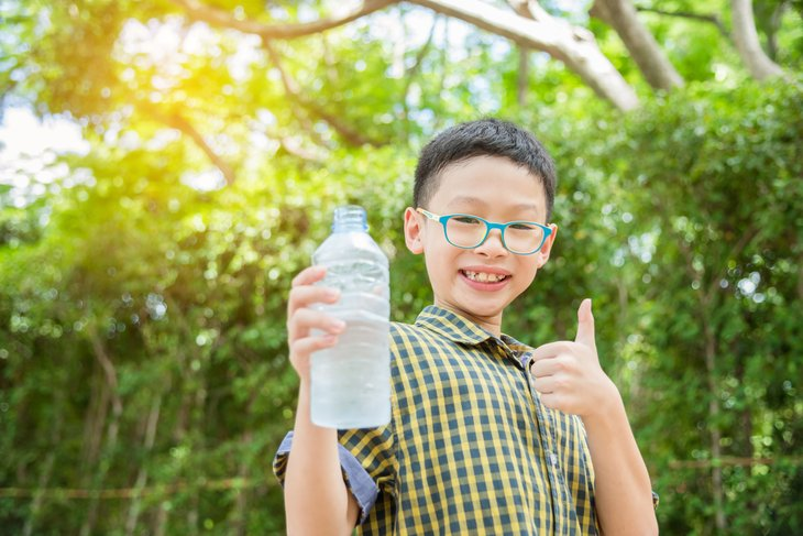 A boy holds a bottle of water
