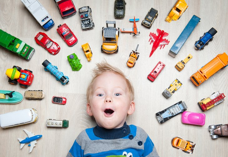 Little boy surrounded by Hot Wheels cars.