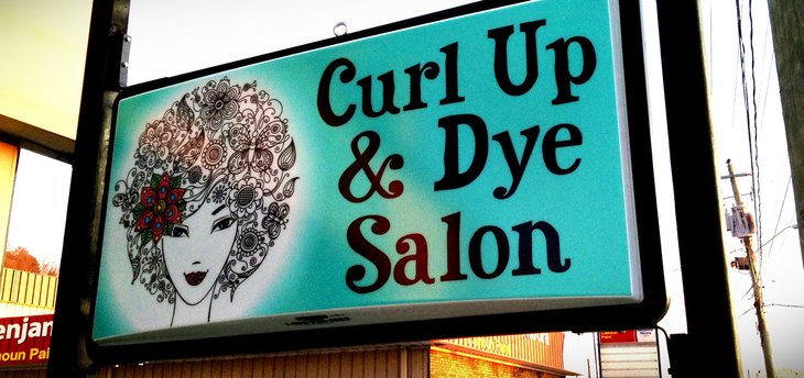 Shop front with sign that says Curl Up and Dye