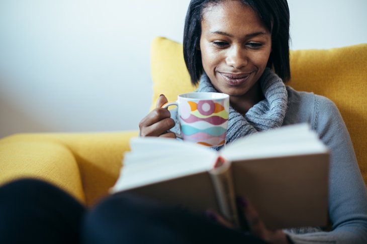 Woman drinking tea and reading a book