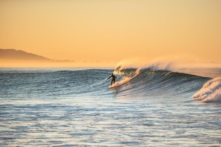 Surfer on a wave, against a golden sky