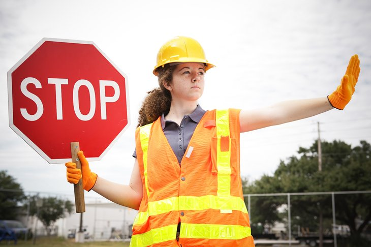 Road construction flagger holding a stop sign and directing traffic.