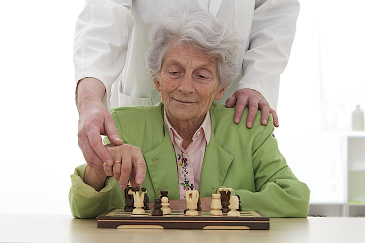 Old woman playing chess, with caregiver helping
