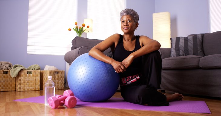 African American woman sitting on floor by exercise ball.
