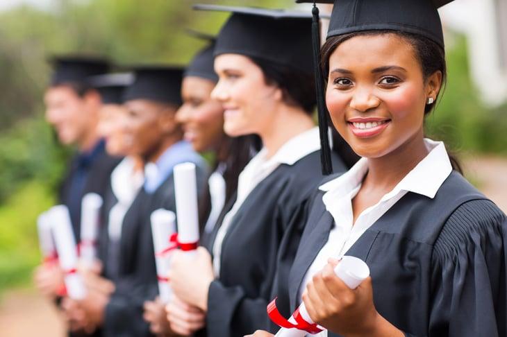 New college graduates pose with their diplomas
