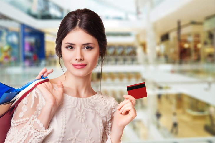 Woman at store, holding a card.