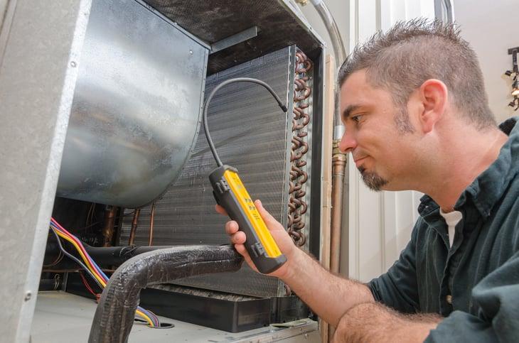 HVAC repairman working on AC unit.