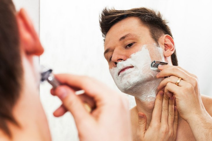 Man looking in mirror, shaving.
