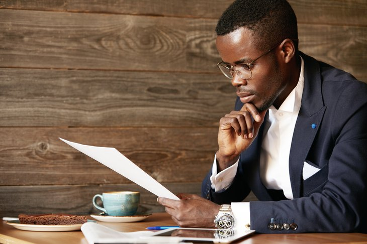 African American man in a suit studying a document