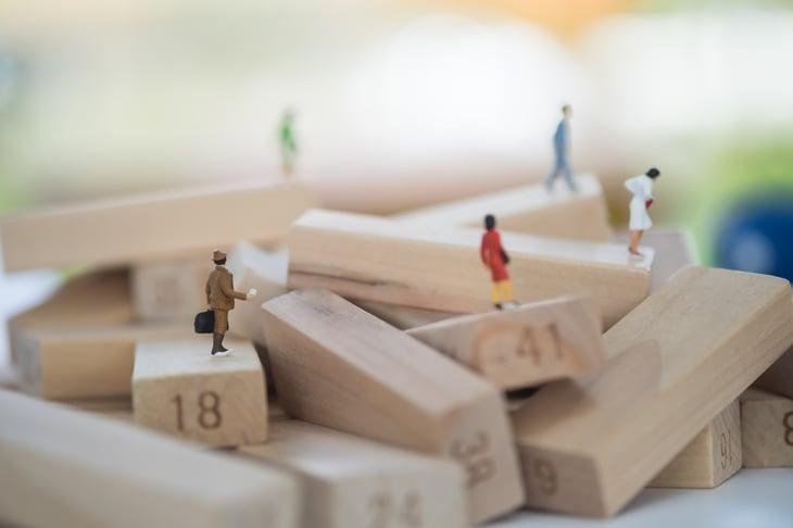 Miniature people on Jenga blocks