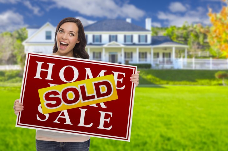 Woman with Home for Sale/Sold sign.