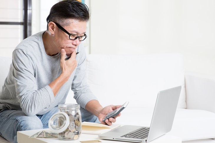 Man using laptop and calculator to plan finances
