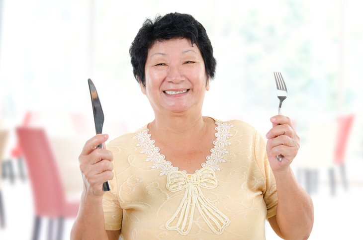 A senior Asian woman holds up a knife and fork at a restaurant