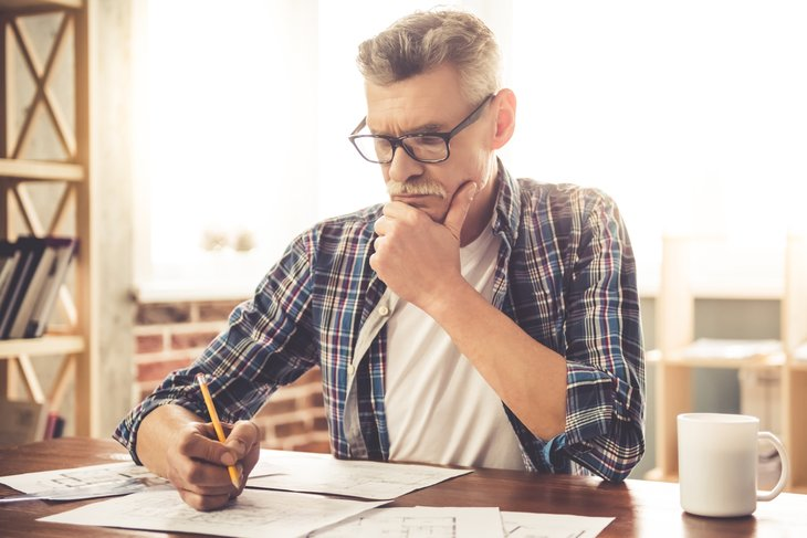 Senior man at writing desk.