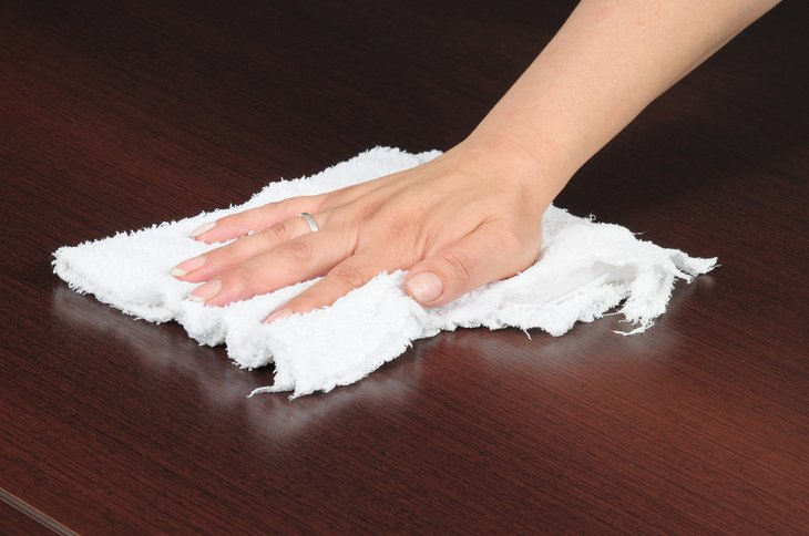 Hand with rag cleaning table top